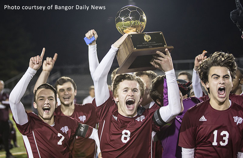 picture of boys soccer team members holding trophy